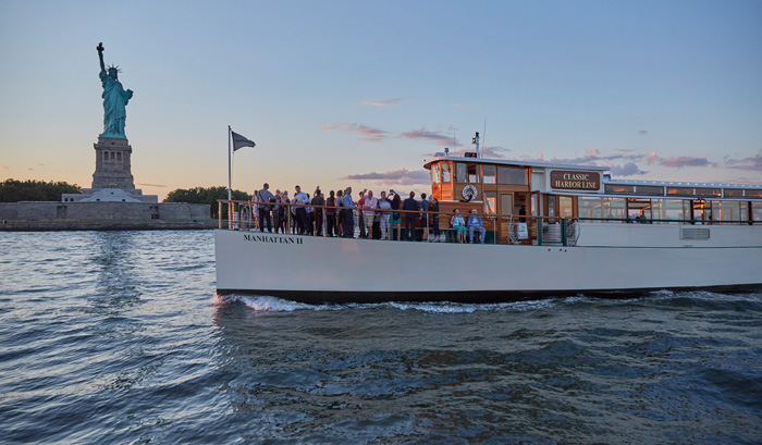 Sunset Cruise with guests on the bow of yacht Manhattan II at the Statue of Liberty